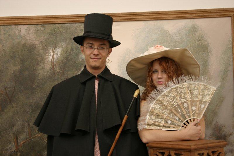 Мужчина в плаще и девушка в шляпке и с веером.